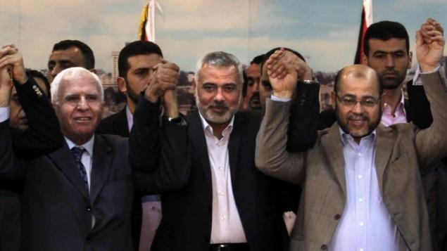 (de gauche à droite) Le chef de la délégation du Fatah Azzam al-Ahmad, le Premier ministre du Hamas dans la bande Gaza Ismail Haniyeh et l'adjoint du chef politique du Hamas Moussa Abu Marzouk après un accord entre les dirigeants de la Cisjordanie et de la bande de Gaza pour la formation d'un gouvernement d'unité sous cinq semaines, à Gaza Ville, le 23 avril 2014. (Crédit : AFP/Said Khatib)