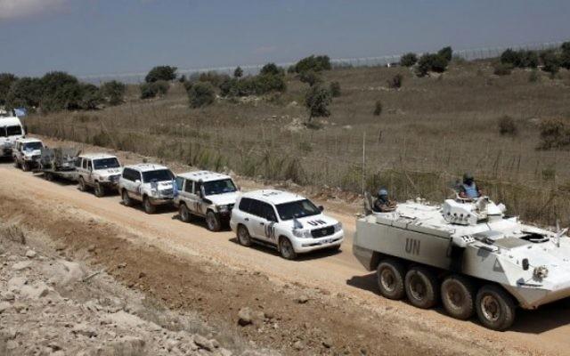 Un convoi de la Force des Nations unies chargée d'observer le dégagement (FNUOD) quitte le côté syrien du plateau du Golan pour Israël, le  15 septembre 2014. (Crédit : AFP/Jalaa Marey)