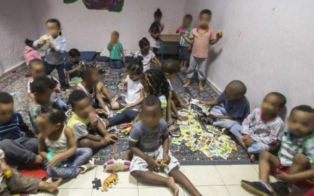 """Des enfants de familles de migrants africains rassemblées dans une """"crèche"""" dans le sud de Tel Aviv, le 28 mai 2015. Caractérisée par une saleté et une misère noire, elles ont toutes été dénoncées par des associations de défense des droits de l'Homme et les médias comme des """"entrepôts à bébé"""". Les visages des enfants ont été floutés pour protéger leurs identités. (Crédit : AFP/Jack Guez)"""