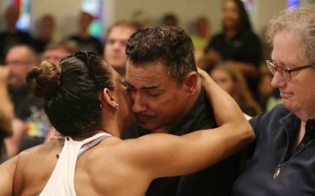 Une femme prend dans ses bras un homme blessé par la fusillade au Pulse pendant un service en mémoire des victimes de l'attentat terroriste à l'église Joy MCC à Orlando, en Floride, le 12 juin 2016. (Crédit : Joe Raedle/Getty Images/AFP)