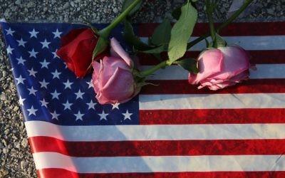 Des roses et un drapeau américain posés sur l sol près du Pulse, le club d'Orlando où Omar Mateen a tué 49 personnes et en a blessé 53, le 13 juin 2016. (Crédit : Joe Raedle/Getty Images/AFP)