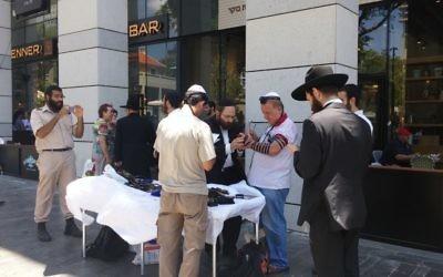 Des membres du Chabad invitent les hommes à porter des tefillin, sur le site de l'attaque terroriste du mercredi 8 juin, au marché Sarona à Tel-Aviv, le 9 juin 2016 (Crédit : Ricky Ben-David)