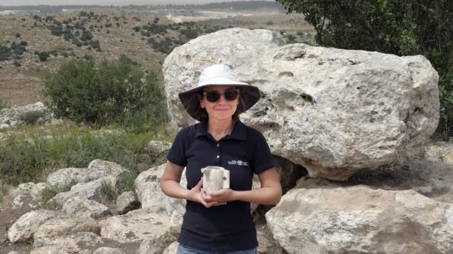Jenny Marcus, archéologue de l'Autorité israélienne des Antiquités, avec un récipient en calcaire de l'époque du Deuxième Temple qui a été découvert dans le domaine agricole. Photographie publiée le 7 juin 2016. (Crédit : Avraham Tendler)