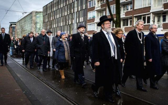 le maire d'Amsterdam Eberhard van der Laan (4e à droite) pendant une marche entre la mairie et le monument d'Auschwitz au parc Wertheimpark d'Amsterdam le 26 janvier 2014, pendant la Journée nationale du souvenir des victimes de l'Holocauste. (Crédit : AFP Photo/ANP/Remko de Waal via JTA)