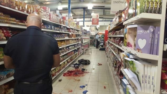Un policier israélien documente les preuves de la scène d'une attaque au couteau dans le supermarché Rami Levy du parc industriel du Shaar Binyamin, au nord de Jérusalem, le 18 février 2016. (Crédit : police israélienne)