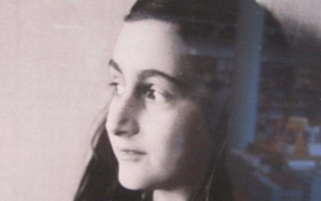 Photographie prise dans la librairie de la maison d'Anne Frank, avec sa photo et des copies traduites de son journal en arrière-plan. (Crédit : Matt Lebovic/Times of Israël)