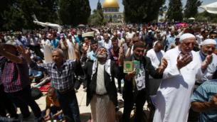 Des fidèles musulmans palestiniens prient devant le Dôme du Rocher sur le Mont du Temple de Jérusalem avant la troisième prière du vendredi du mois sacré du jeûne musulman du Ramadan, le 24 juin 2016. (Crédit : AFP/Ahmad Gharabli)