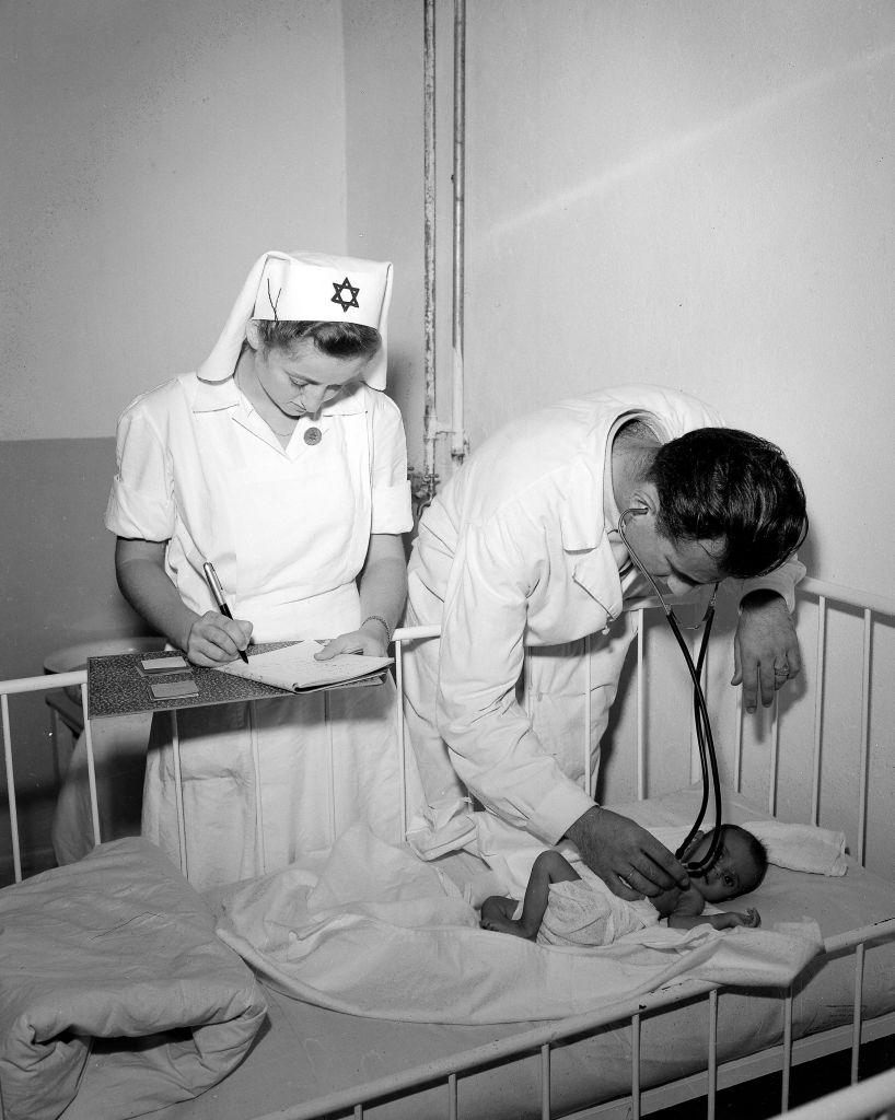 Un médecin israélien examine le bébé dénutri d'une immigrante, en 1949. (Crédit : Teddy Brauner/GPO)