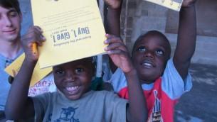 Des enfants haïtiens se réjouissent d'avoir reçu des cahiers Ecojot donnés par l'organisation d'Erin Schrode, le Cartable, qui fournit aux enfants démunis des fournitures écologiques. Septembre 2011. (Crédits : Facebook / The Schoolbag)