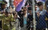 Photo d'illustration : Des enfants derrière une clôture, dans le camp pour migrants de Moria, transformé par la police en centre de détention, à Mytilene, sur l'île de Lesbos, en Grèce, le 3 avril 2016. (Crédit : Aris Messinis/AFP)