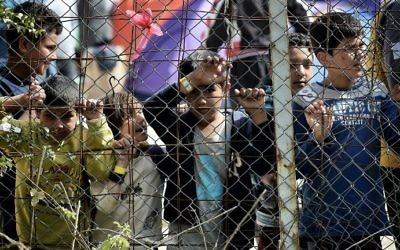 Illsutration : Des enfants derrière une clôture, dans le camp pour migrants de Moria, transformé par la police en centre de détention, à Mytilene, sur l'île de Lesbos, en Grèce, le 3 avril 2016. (Crédit : Aris Messinis/AFP)