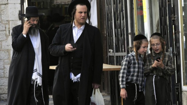 Juifs ultra-orthodoxes au téléphone dans le quartier de Mea Shearim, à Jérusalem. (Crédit : Serge Attal/Flash90)