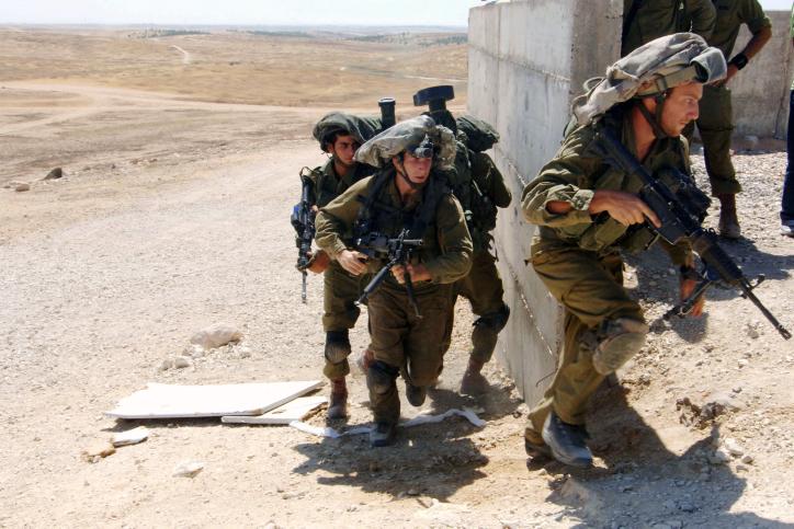 Des soldats de la brigade des parachutistes s'entraînent au combat en porte-à-porte dans les zones inhabitées de Tzeelim, dans le sud d'Israël, le 10 juillet 2014. (Crédit : Flash90)