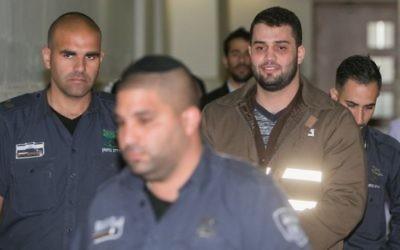 Bilal Abu Ghanem sous escorte, à la cour du district de Jérusalem, le 13 mars 2016. (Crédit : Yonatan Sindel/Flash90)