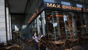 Une femme nettoie les tables au restaurant Max Brenner du marché Sarona, dans le centre de Tel Aviv, le 9 juin 2016, au lendemain matin de l'attaque terroriste qui s'y est déroulée (Crédit : Miriam Alster/Flash90)