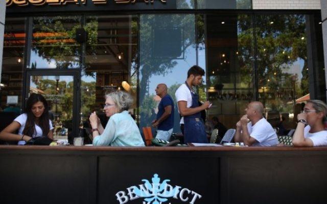 Des Israéliens mangent au restaurant Benedict du centre commercial Sarona, dans le centre de Tel Aviv, quelques heures après une fusillade terroriste qui y a tué quatre personnes, le 9 juin 2016. (Crédit : Miriam Alster/Flash90)
