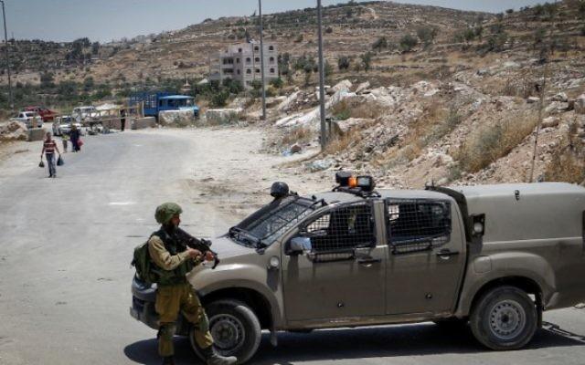 Soldats israéliens à un checkpoint à l'entrée du village palestinien de Yatta, en Cisjordanie, le 9 juin 2016. (Crédit : Wisam Hashlamoun/Flash90)