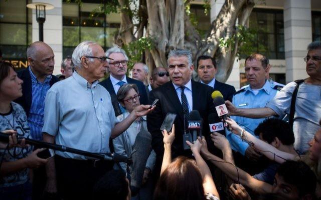 Le leader de Yesh Atid Yair Lapid parle à la presse, entouré de diplomates étrangers après avoir visité le restaurant Max Brenner, le site d'une attaque terroriste le 8 juin au marché de Sarona, Tel Aviv, le 10 juin, 2016. (Crédit : Miriam Alster / Flash90)