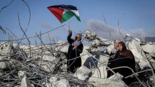La mère du terroriste palestinien Morad Bader Abdullah Adais brandit un drapeau palestinien en se tenant sur les ruines de leur maison après sa démolition par l'armée israélienne à Yatta, au sud de Hébron, en Cisjordanie, le 11 juin 2016. Adais avait poignardé à mort Dafna Meir, mère de six enfants, en janvier. (Crédit : Wisam Hashlamoun/Flash90)