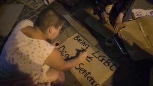 De jeunes militants israéliens LGBT préparent des panneaux pour un rassemblement sur la place Zion de Jérusalem en solidarité avec les victimes de la fusillade terroriste d'Orlando, le 12 juin 2016. (Crédit : Hadas Parush/Flash90)
