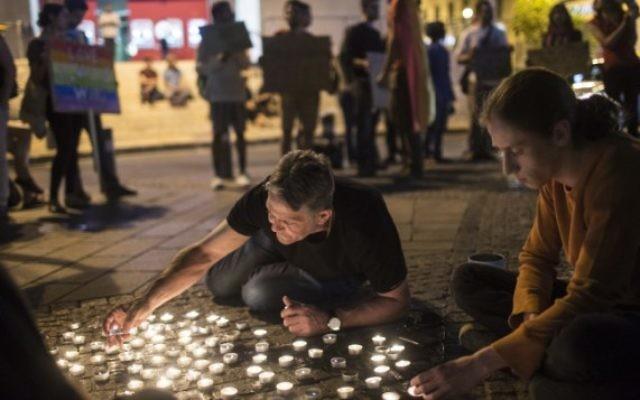 De jeunes militants israéliens LGBT allument des bougies pendant un rassemblement sur la place Zion de Jérusalem en solidarité avec les victimes de la fusillade terroriste d'Orlando, le 12 juin 2016. (Crédit : Hadas Parush/Flash90)