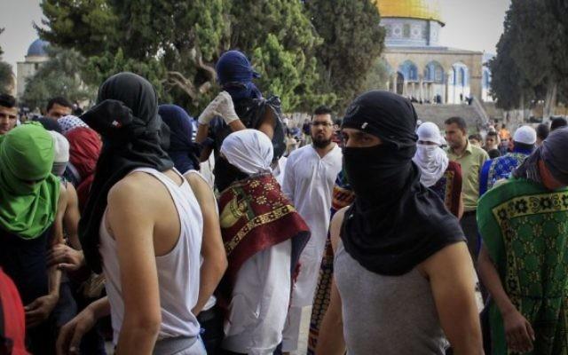 Des Palestiniens masqués avec des pierres pendant des affrontements avec la police sur le mont du Temple, dans la Vieille Ville de Jérusalem, le 28 juin 2016. (Crédit : Muammar Awad/Flash90)