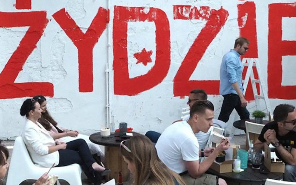 Des gens mangeant au restaurant israélien Jaffa à Lodz, en Pologne -avec le mot 'Juif' en arrière-plan le 11 juin 2016. (Autorisation de Rafal Betlejewski / via JTA)