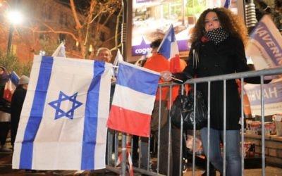 Des juifs français agitant des drapeaux israéliens et français devant l'Hyper Cacher un an après que quatre clients juifs aient été assassinés lors d'un attentat terroriste dans le magasin casher Paris, 9 janvier 2016. (Crédit photo: Serge Attal / Flash90)