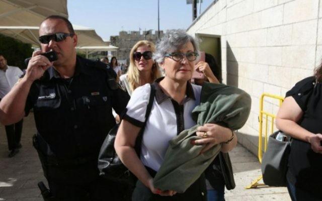 Leslie Sachs, directrice des Femmes du Mur, porte un rouleau de Torah pendant qu'elle est escortée par des policiers à l'écart du mur Occidental, à Jérusalem, le 7 juin 2016. (Crédit : Michal Fattal)