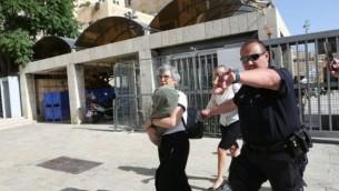 Leslie Sachs, directrice exécutive des Femmes du Mur, porte un rouleau de Torah pendant qu'elle est escortée par des policiers à l'écart du mur Occidental, à Jérusalem, le 7 juin 2016. (Crédit : Michal Fattal)