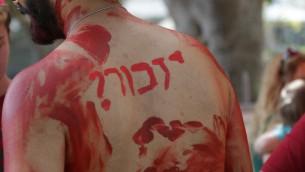 """Un homme à la gay pride avec un tatouage où l'on peut lire """"Souvenir"""", à Tel Aviv, le 3 juin 2016 (Crédit : Luke Tress/Times of Israel)"""