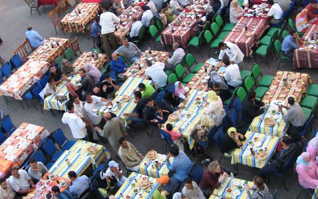 Des musulmans attentent le coucher du soleil pour commencer le repas de l'iftar, pendant le mois de Ramadan, au Caire, en 2005. (Crédits : Wiki Commons)
