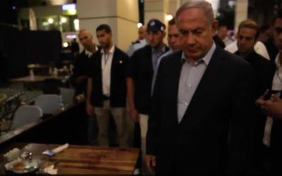 Le Premier ministre Benjamin Netanyahu sur les lieux d'un attentat au marché Sarona de Tel Aviv, le 8 juin 2016. (Crédit : bureau du Premier ministre)