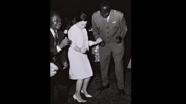 Miriam Eshkol, l'épouse du Premier ministre Levi Eshkol, danse avec le ministre ougandais des Affaires étrangères Sam Odaka et les chef des armées et futur président Idi Amin pendant une visite sur une base militaire proche de Kampala, en juin 1966. (Crédit : GPO)