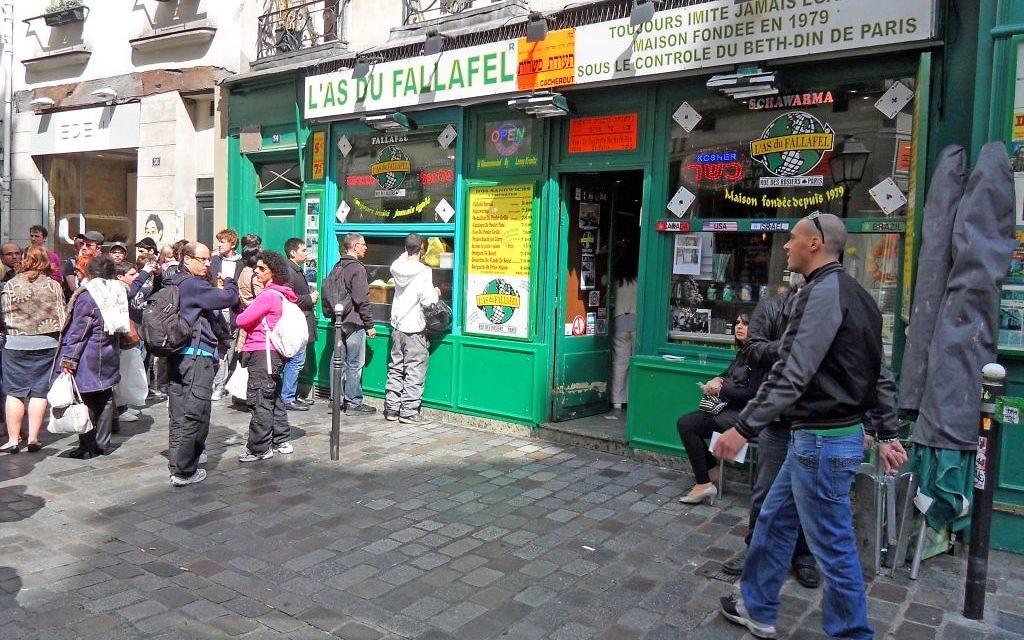 Yomi Peretz, à droite, s'approche de la queue de clients attendant de pouvoir commander à l'As du Fallafel, dans le quartier juif historique de Paris, en avril 2012. (Crédit : WikiCommons)