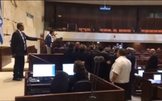 La députée Hanin Zoabi (au centre), de la Liste Arabe Unie, confronte ses camarades parlementaires en assemblée de la Knesset après ses remarques sur l'accord de réconciliation entre la Turquie et Israël, le 29 juin 2016. (Crédits  : capture d'écran YouTube)