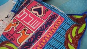 Les couvertures de challah combinent des tissus et des symboles traditionnels ghanéens avec l'hébreu. (Crédit: Melanie Lidman / Times of Israel)