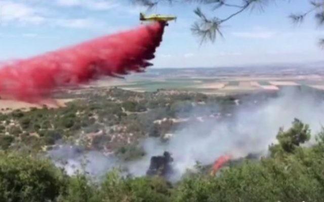 Pompiers luttant contre un incendie près du carrefour Megiddo, dans le nord d'Israël, le 11 juin 2016. (Crédit : capture d'écran Facebook)