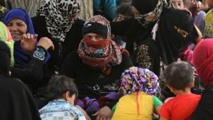 Des Irakiens déplacés, qui fuient le village d'al-Falahat, à l'ouest de Fallouja, en raison des combats entre l'armée irakienne et l'Etat islamique, attendent de recevoir de la nourriture et de l'aide au village d'al-Azraqiyah, le 4 juin 2016. (Crédit : AFP PHOTO/AHMAD AL-RUBAYE)