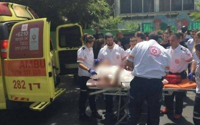 Un garçon de 14 ans se fait évacuer vers l'hôpital après avoir été blessé par un pétard, à l'extérieur d'une école maternelle de Tel Aviv, le 8 juin 2016 (Crédit : Moshiko Moskowitz/MDA)