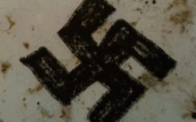 Un graffiti de croix gammée trouvé sur une aire de jeu pour enfants du quartier de Stamford Hill, à Londres. (Crédit : Shomrim)