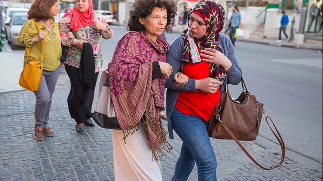 Annie Kurland et une collègue enseignante au marché Mahane Yehuda de Jérusalem en 2016, dans le cadre du projet de coexistence Salle des profs 2016, qui comprend une exposition de photos visible au YMCA de Jérusalem. (Crédit : Dana Talel)