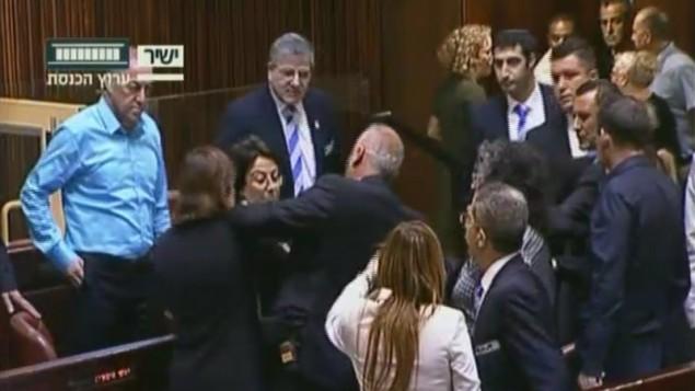 Altercation entre la députée Hanin Zoabi de la Liste arabe unie, au centre, et d'autres élus en séance plénière de la Knesset après son discours sur l'accord de réconciliation entre Israël et la Turquie, le 29 juin 2016. (Crédit : capture d'écran Chaîne de la Knesset)