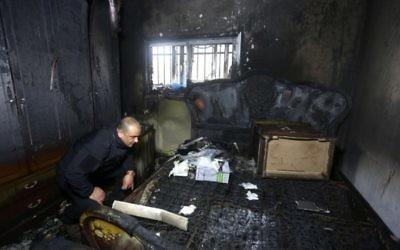 Un policier palestinien inspecte les dommages dans la maison incendiée d'un témoin clé au procès pour incendie criminel et meurtre de deux extrémistes juifs après une attaque de juillet 2015 à Duma, qui a fait trois morts palestiniens, un bébé et ses parents, à Duma, en Cisjordanie, le 20 mars 2016. (Crédit : AFP/Jaafar Ashtiyeh)