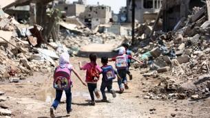 Des enfants syriens scolarisés passent devant des immeubles en ruine  à Jobar, fief rebelle, en banlieue est de la capitale Damas, le 30 avril 2016. (Crédit : AFP/Amer Almohibany)