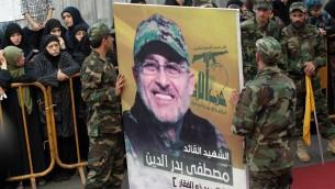 Les membres du groupe terroriste chiite libanais Hezbollah portent un portrait de Mustafa Badreddine, un haut commandant du Hezbollah qui a été tué dans une attaque en Syrie, lors de ses funérailles dans le quartier Ghobeiry du sud de Beyrouth, le 13 mai 2016. (Crédit : AFP / ANWAR AMRO)