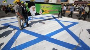Des Irakiens sur le drapeau israélien montrent une banderole portant la photo du Guide suprême iranien, l'Ayatollah Ali Khamenei, pendant qu'ils participent à la Journée al-Quds [Jérusalem], à Bagdad, le 1er juillet 2016. (Crédit : AFP/Ahmad al-Rubaye)
