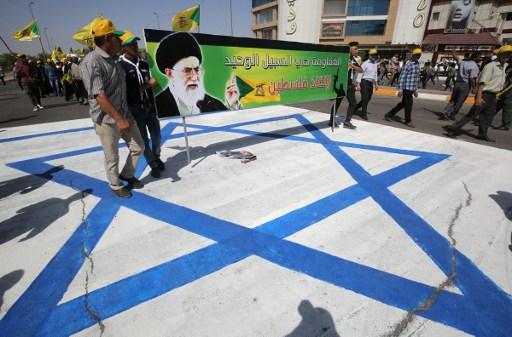 Des Irakiens sur le drapeau israélien montrent une banderole portant la photo du Guide suprême iranien, l'Ayatollah Ali Khamenei, pendant qu'ils participent à la Journée al-Quds (Jérusalem), à Bagdad, le 1er juillet 2016. (Crédit : AFP/Ahmad al-Rubaye)