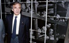 Elie Wiesel, auteur, prix Nobel de la Paix et survivant de la Shoah, devant une photo de lui (3e à droite, en bas) et d'autres détenus au camp de concentration de Buchenwald en 1945, pendant sa visite au musée et mémorial de l'Holocauste Yad Vashem, à Jérusalem, le 18 décembre 1986. (Crédit : AFP/Sven Naxkstrand)