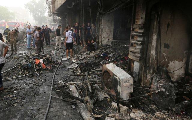 Des Irakiens inspectent les dégâts après une attaque à la voiture piégée revendiquée par l'Etat islamique qui a fait de nombreux morts dans le quartier central de Karrada, à Bagdad, le 3 juillet 2016 (Crédit : Sabah Arar/AFP)
